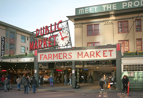 Pike Place Market's main entrance. A red neon sign says Public Market over another sign with red letters that says Farmers Market. Several people walk in front of the signs on a brick street.