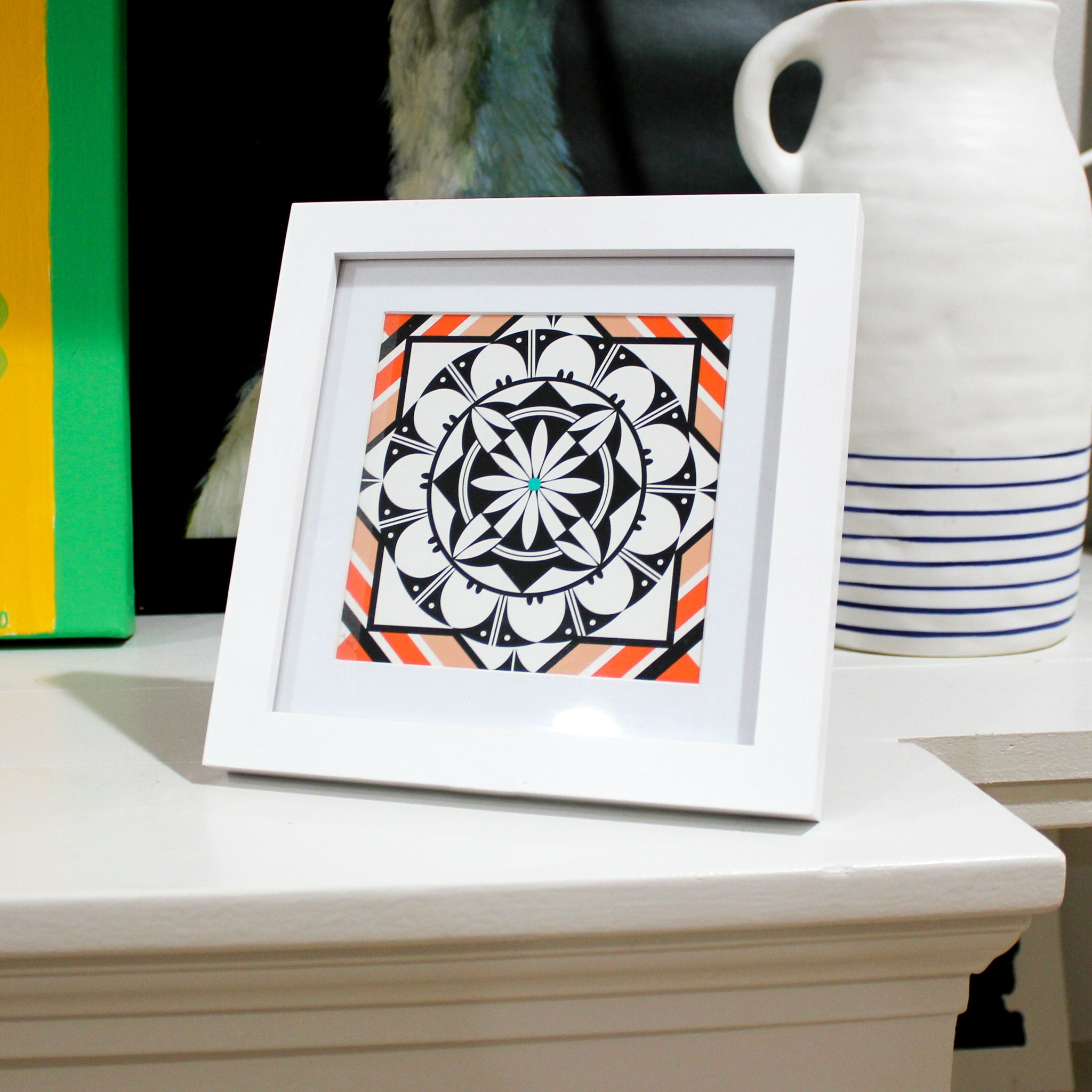 A-black-white-and-orange/red-geometric-design-with-a-flower-in-the-center-sits-on-a-shelf-in-a-white-frame