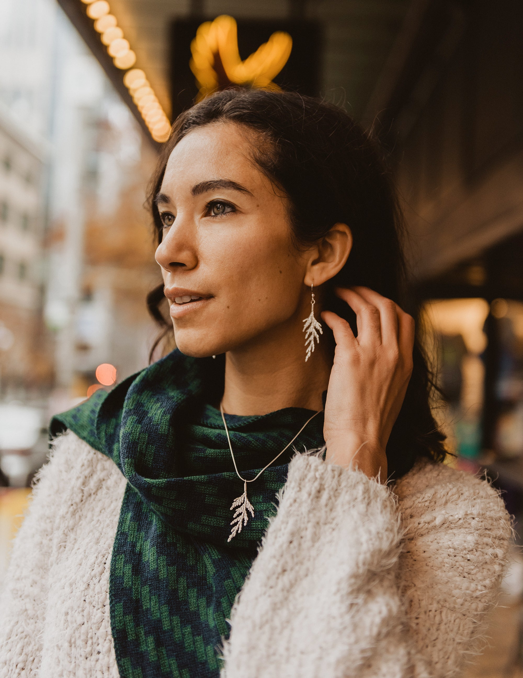 Woman-models-forest-green-and-navy-blue-knit-scarf-and-silver-necklace-and-earrings-featuring-cedar-bough