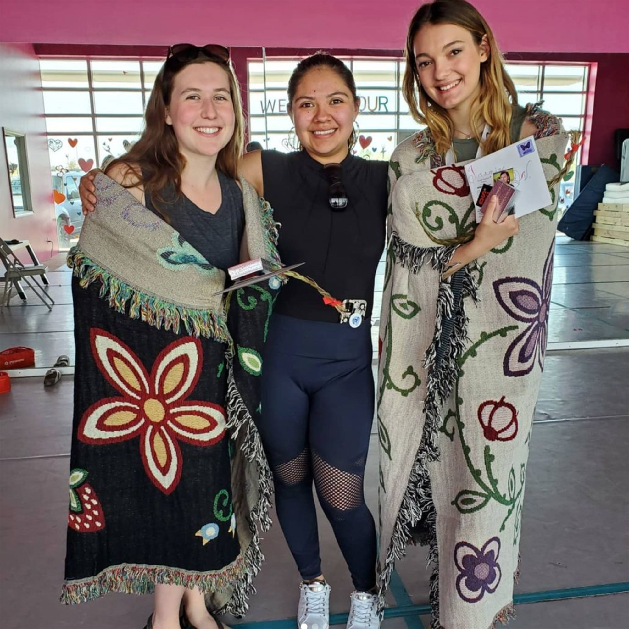 Three-women-stand-smiling-and-graduates-on-either-end-are-wrapped-in-a-black-and-a-beige-throw-blanket-with-woodland-floral-designs
