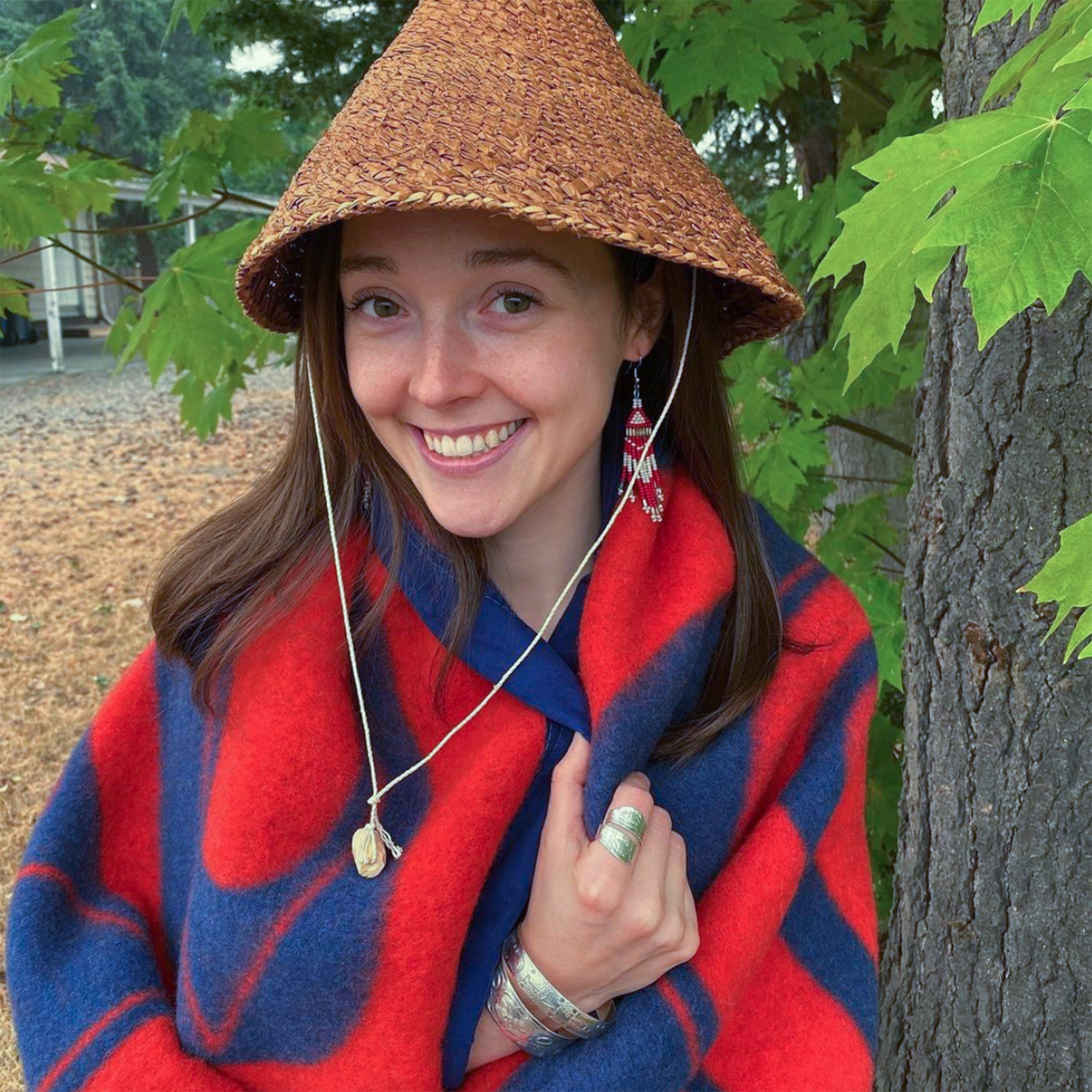A-woman-with-a-cedar-hat-smiles-and-stands-wrapped-in-a-red-and-blue-wool-blanket-with-Northwest-Coast-designs.