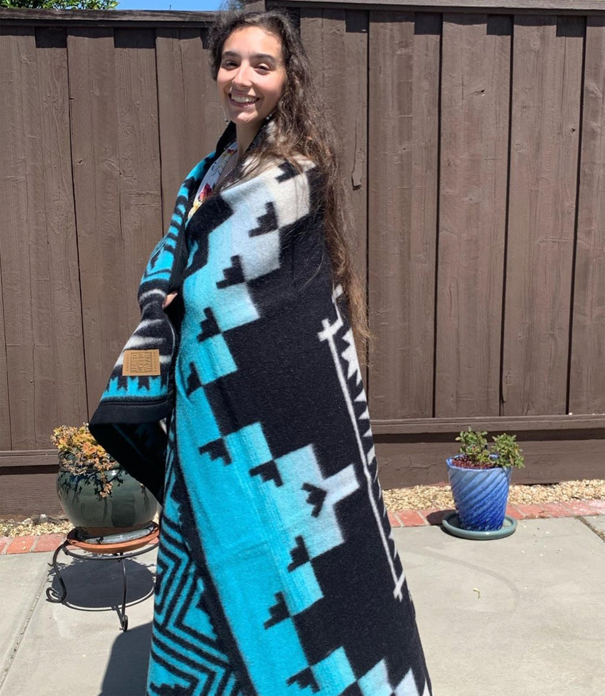 A-woman-with-long-brown-hair-stands-smiling-and-wrapped-in-black-and-turquoise-wool-blanket