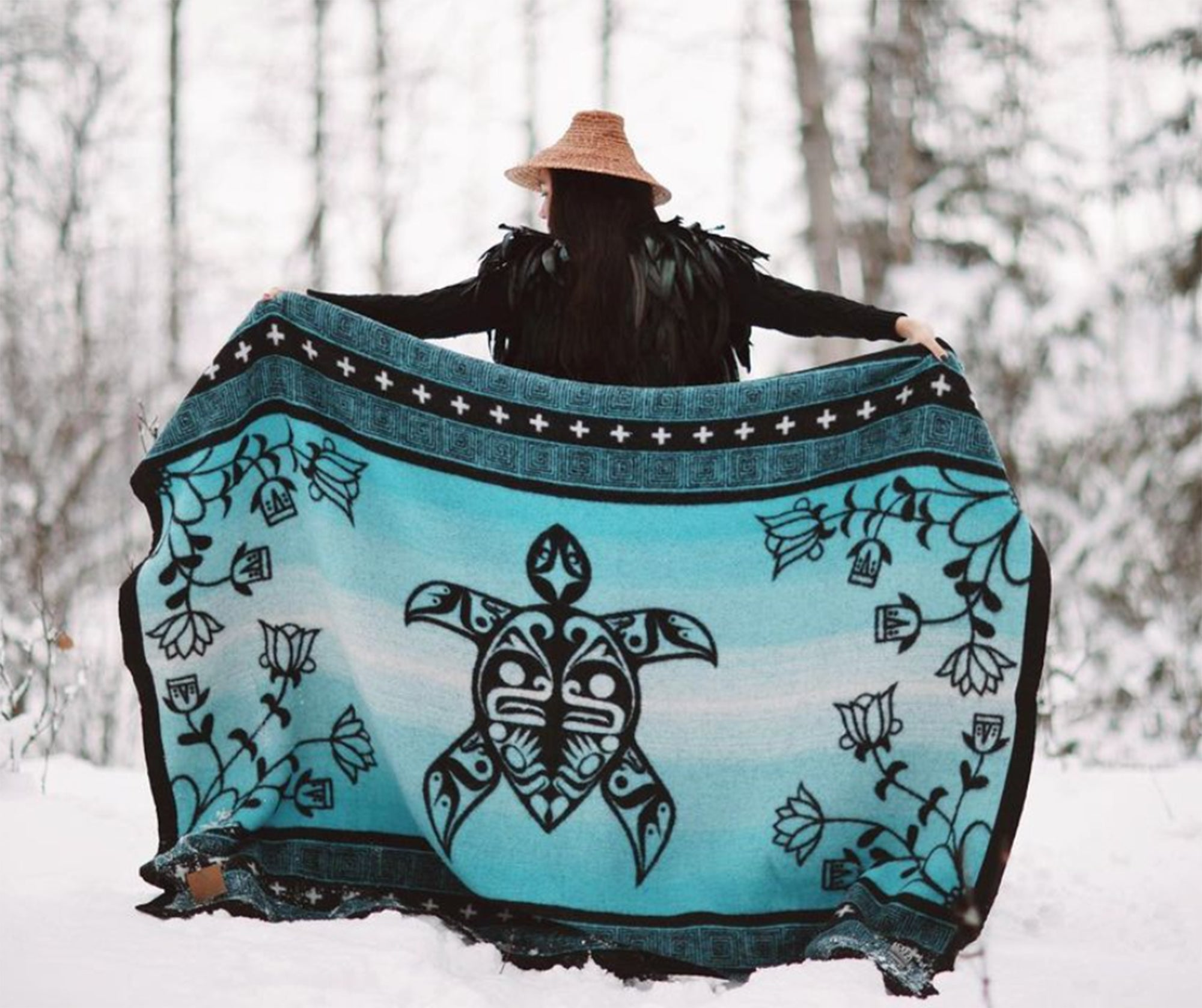 Woman-with-cedar-hat-holds-turquoise-and-black-turtle-design-wool-blanket-stretched-out-behind-her