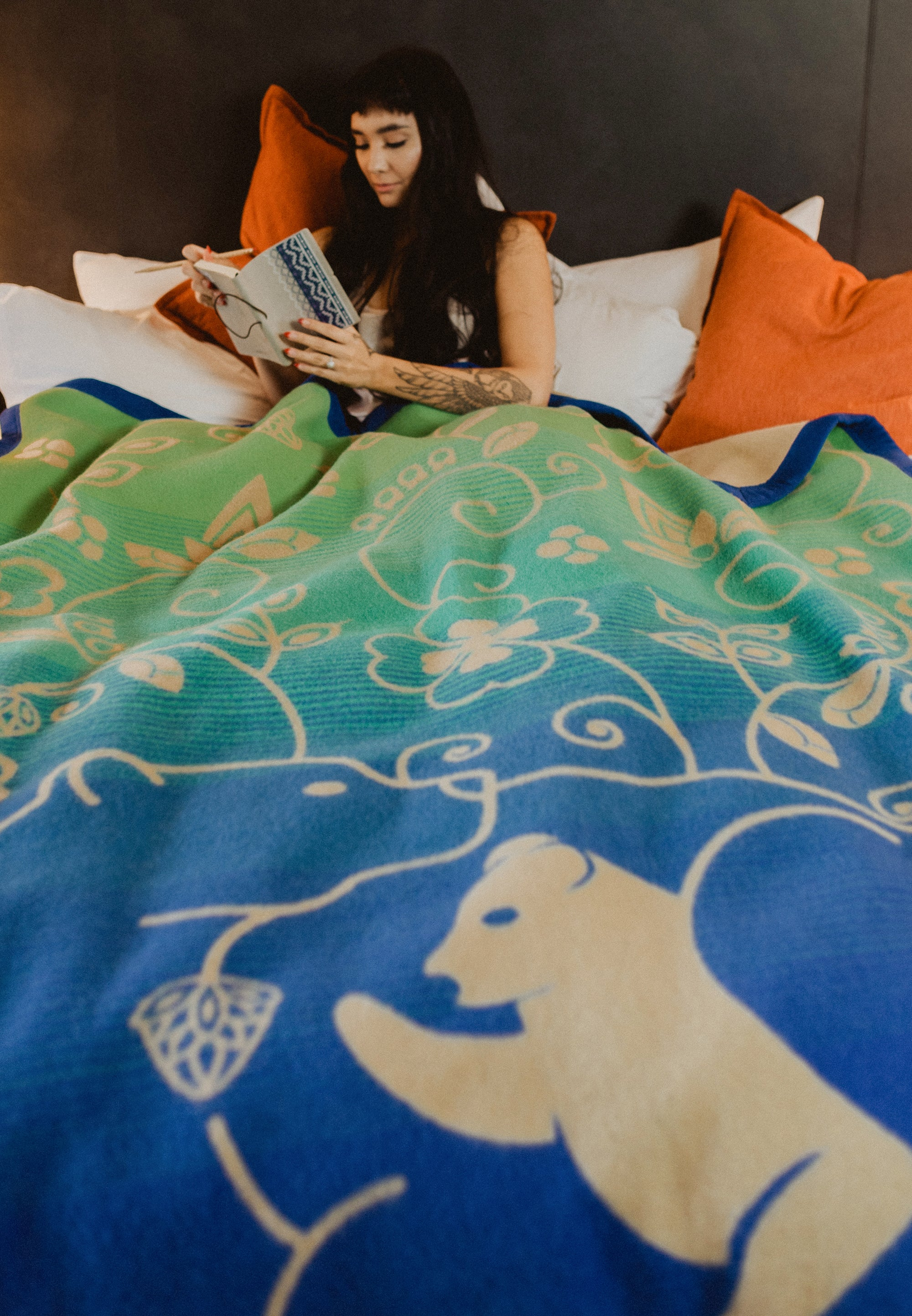 Woman-reads-in-bed-with-blue-tan-and-green-wool-blanket-covering-her.-Blanket-has-bear-and-cub-design-surrounded-by-woodlands-floral