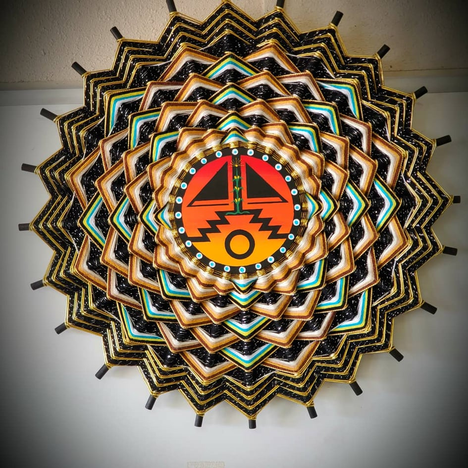 Mandala-featuring-orange-and-black-Navajo-design-in-center-circle-surrounded-by-green-blue-yellow-brown-black-triangle-shaped-weavings