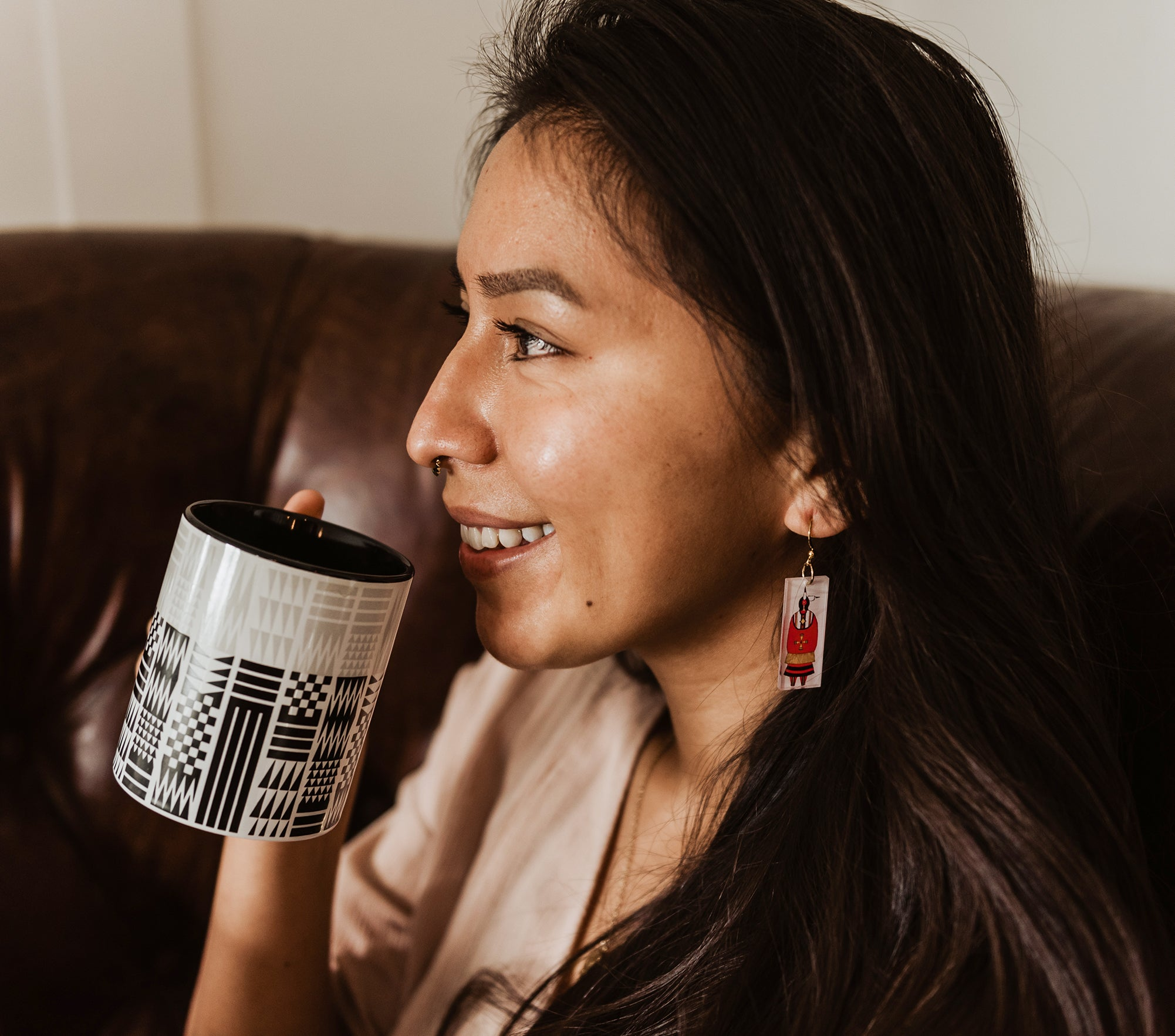 Woman-smiles-holding-black-and-white-Coast-Salish-Pattern-mug-and-wears-white-earrings-with-woman-in-red