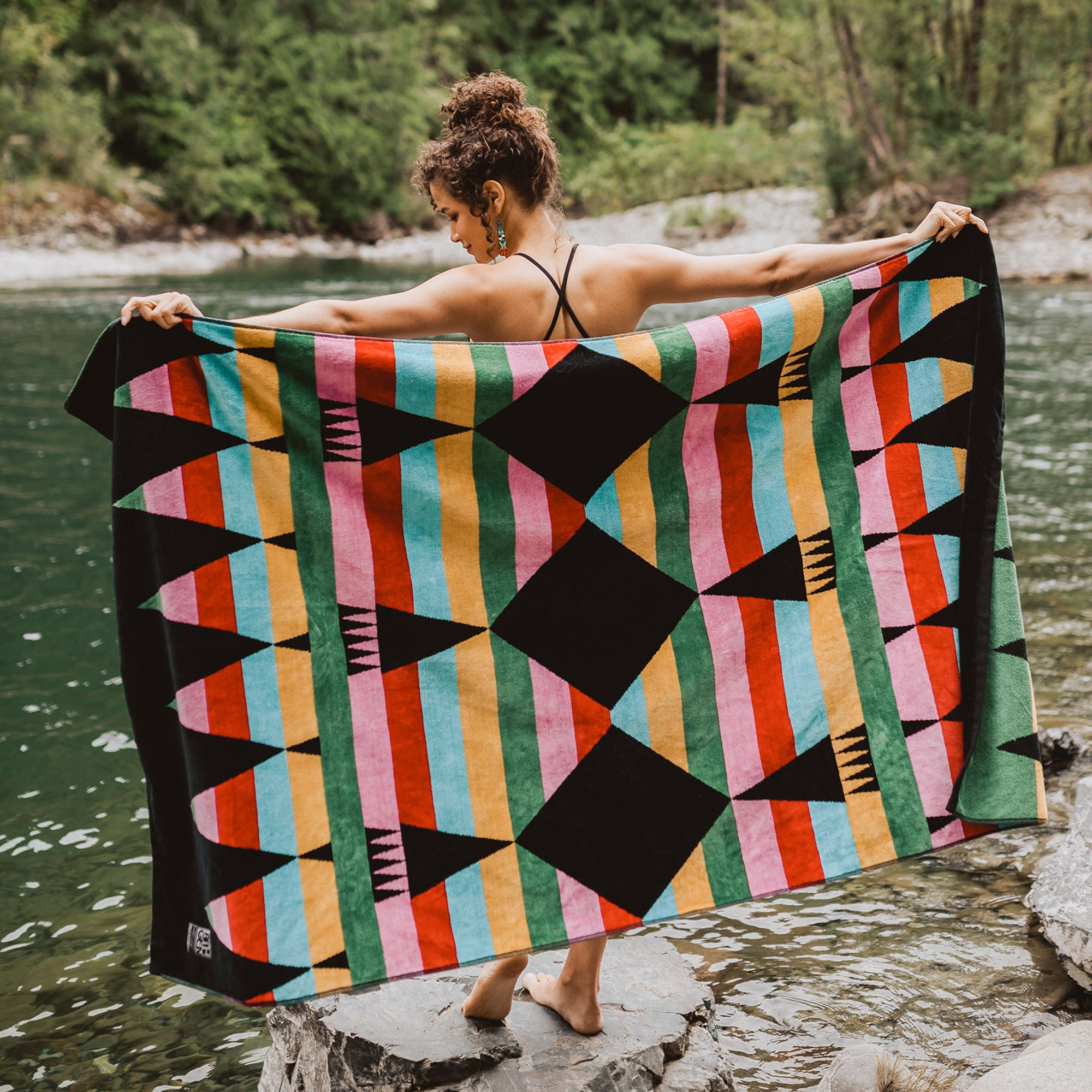 Woman-stands-on-rock-near-water-and-holds-towel-out-behind-her-to-display-the-green-pink-red-blue-orange-ribbons-design
