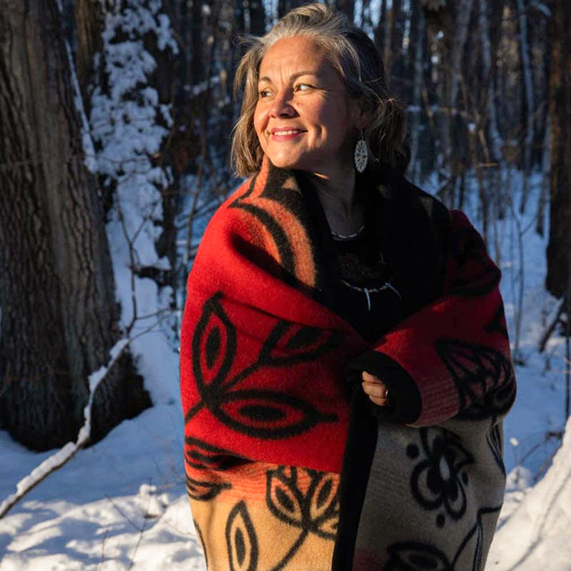 Anishinaabe-arts-entrepreneur-Sarah-Agaton-Howes-stands-in-snow-wrapped-in-black-and-red-renewal-wool-blanket-and-oval-floral-birch-bloom-earrings