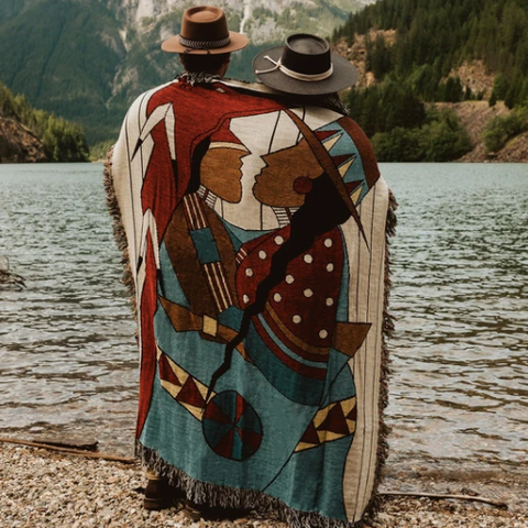 """A man and woman stand with their backs to the camera. They are wrapped in Blackfeet artist John Pepion's """"Snaggin' Blanket"""" which features a Native man and woman embracing."""
