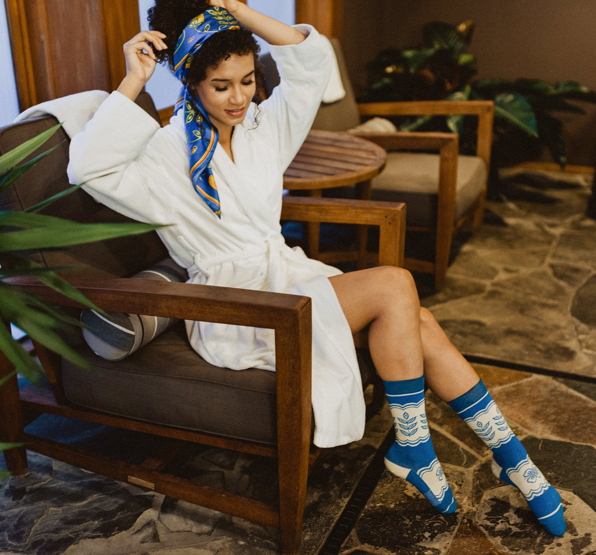 Woman-sits-in-a-white-robe-with-blue-and-white-woodlands-floral-socks-and-blue-green-and-orange-woodlands-floral-silk-scarf-in-hair