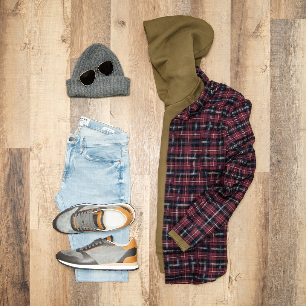 flat lay image of olive alex mill hoodie, grey toque, zegna metal aviator sunglasses, frame finn light wash jeans, brunello cucinelli grey suede sneakers, and red and purple check portuguese flannel shirt