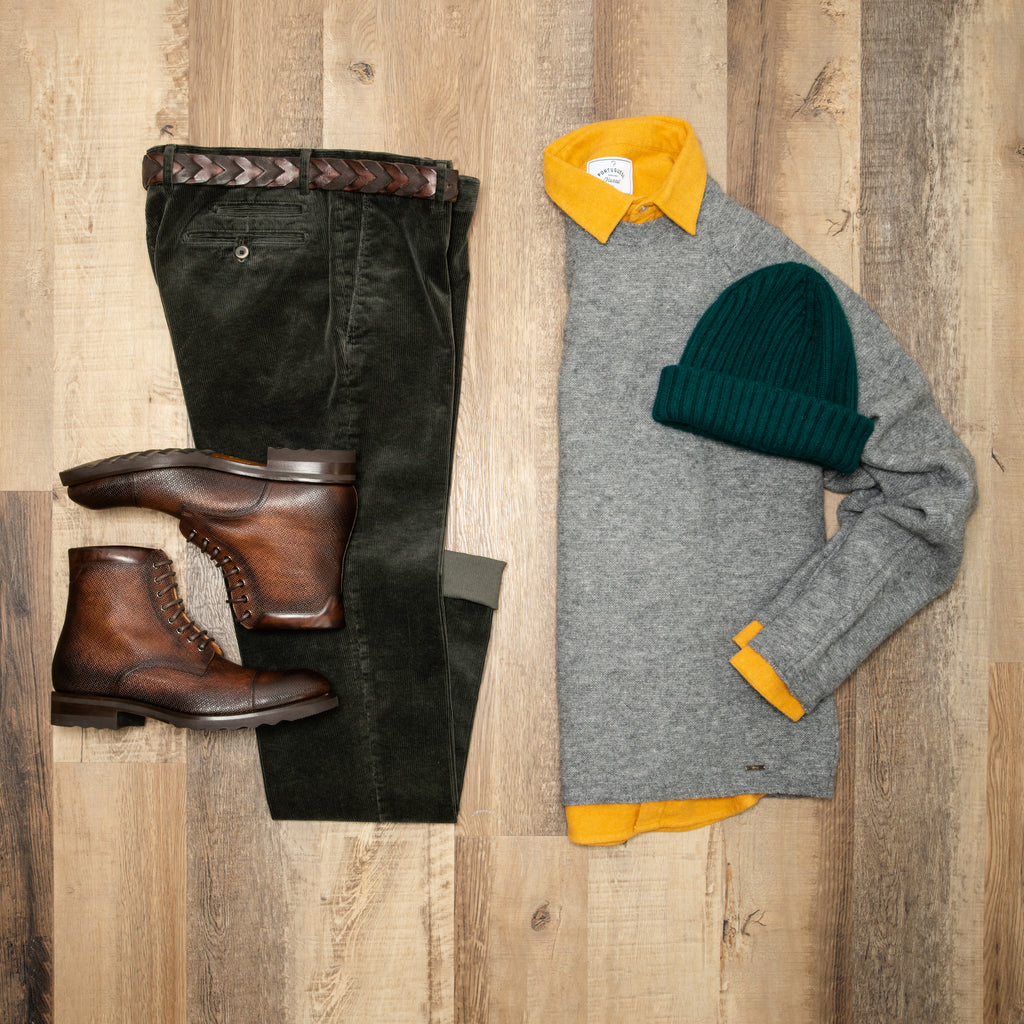 Flat lay image of olive corduroy trousers, brown boots, grey sweater with mustard portuguese flannel shirt under, and a green toque
