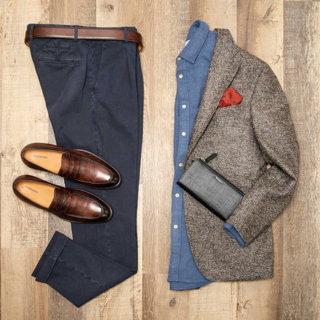 Flat lay photo of navy trousers, brown loafers, light blue portuguese flannel shirt, textured brown sport jacket, and black zegna wallet