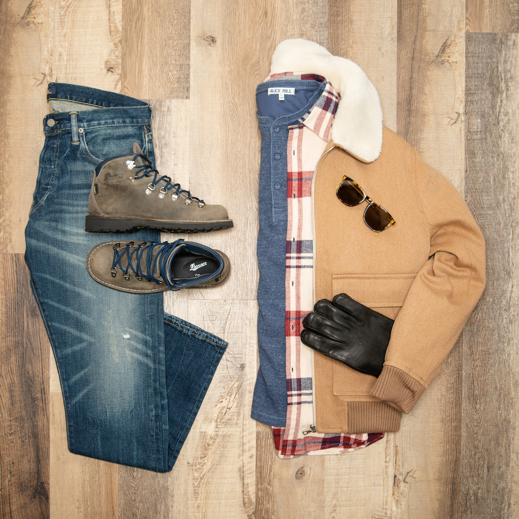 Flat lay image of ralph lauren polo jeans, bronze APC bomber, cream and red portuguese flannel shirt, and blue henley shirt