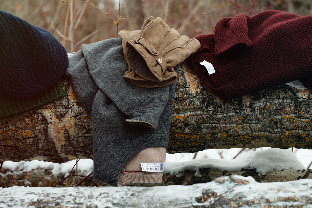 Cashmere sweaters and gloves draped across a tree