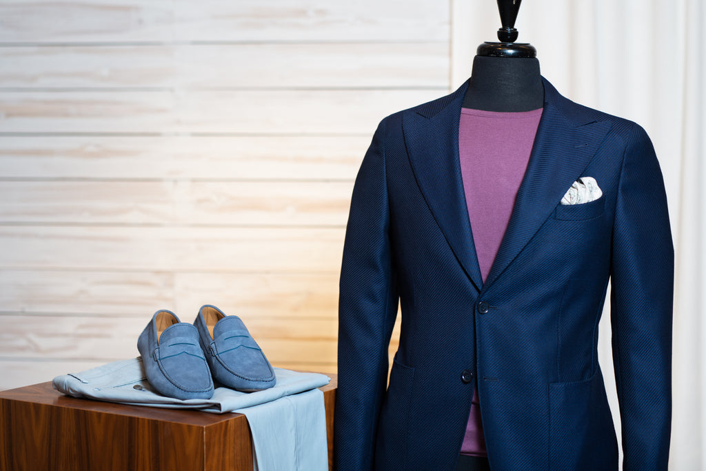 Corneliani CC navy sport jacket worn with light grey trousers, purple knit t-shirt, and blue suede driving shoes