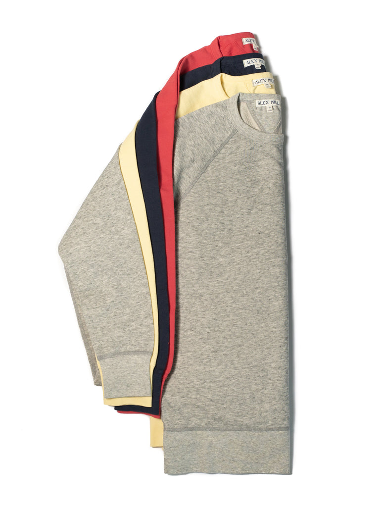 4 Alex Mill sweaters layered on top - grey, yellow, navy, red