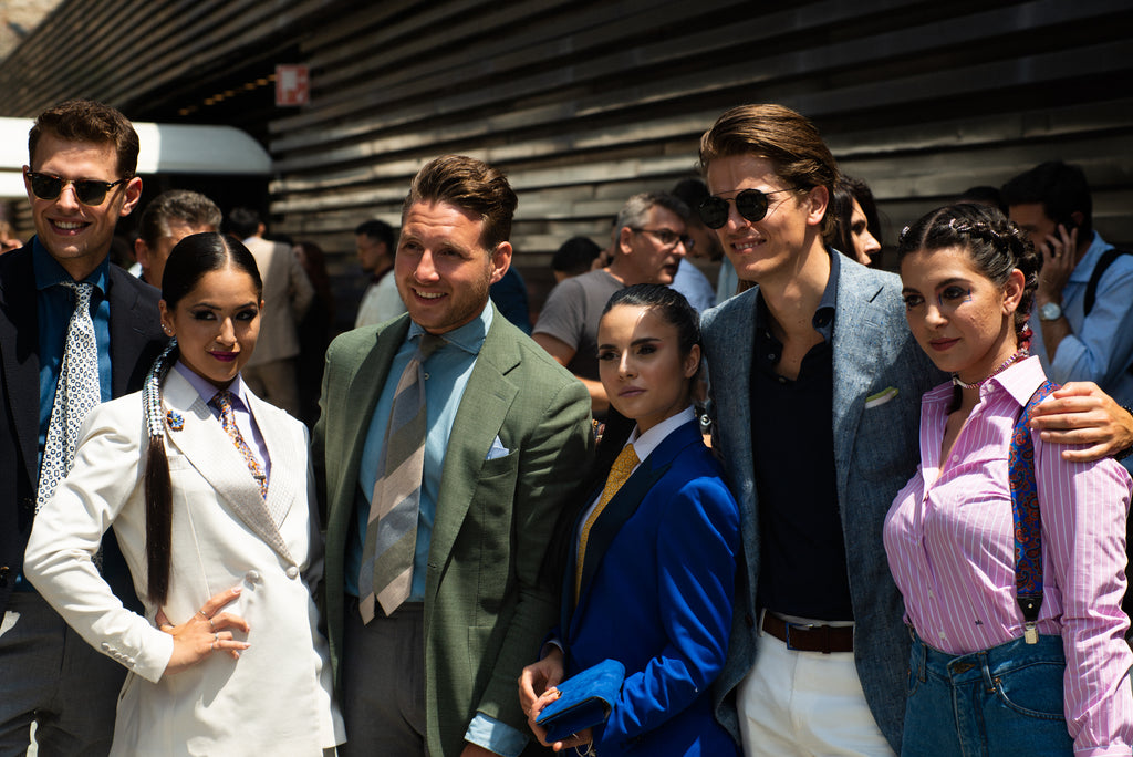 Group of men and women dressed in tailored clothing at Pitti Uomo