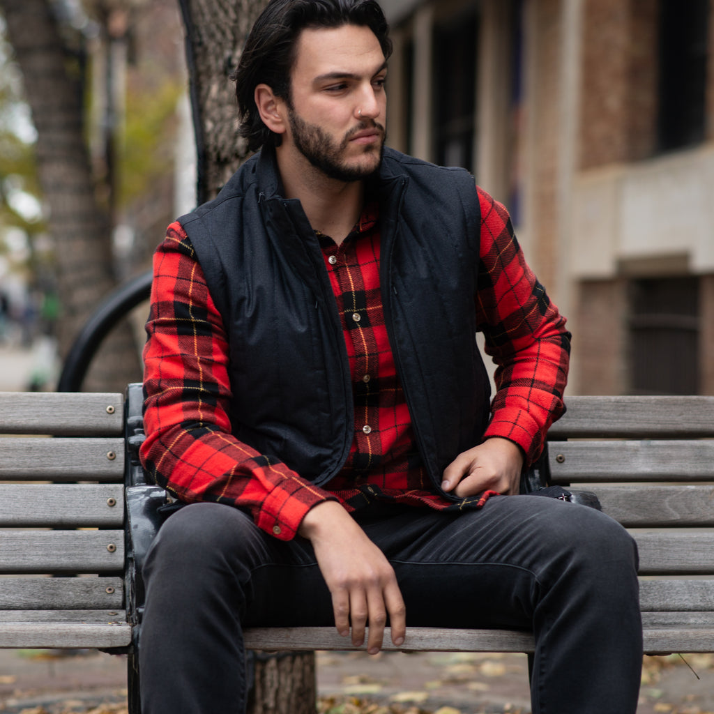 Zach sitting on bench wearing red Portuguese flannel shirt, Corneliani ink navy vest, and frame fade to grey jeans