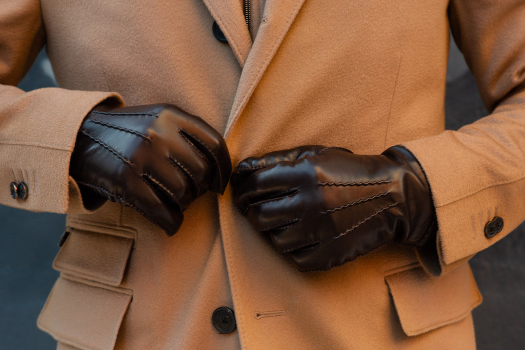 Hestra gloves worn against a Corneliani camel overcoat