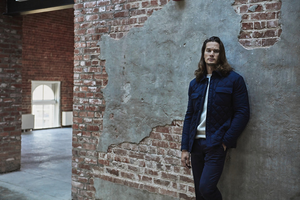 Ermenegildo Zegna - The Helm 2019 campaign - Joey in navy quilted jacket standing by brick wall
