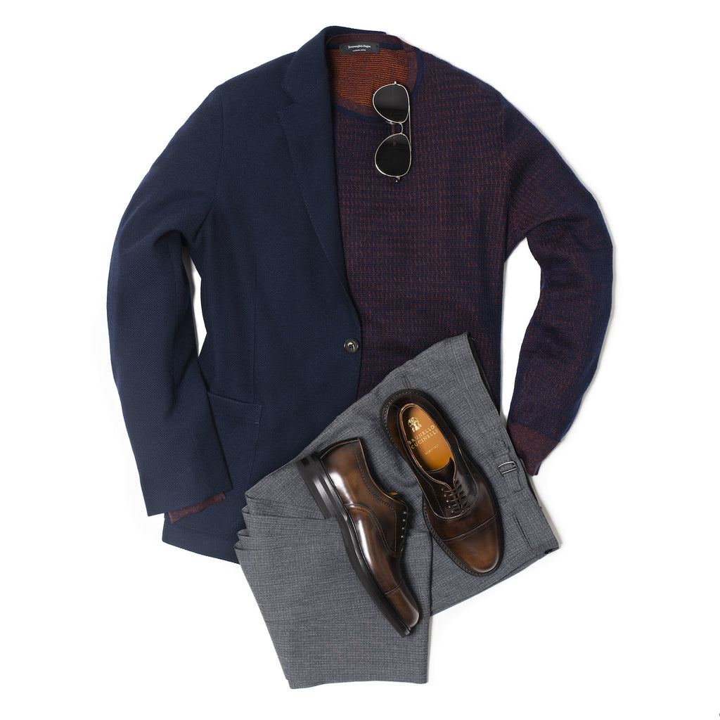Knit zegna crewneck sweater under navy jersey blazer with grey trousers and brown dress shoes