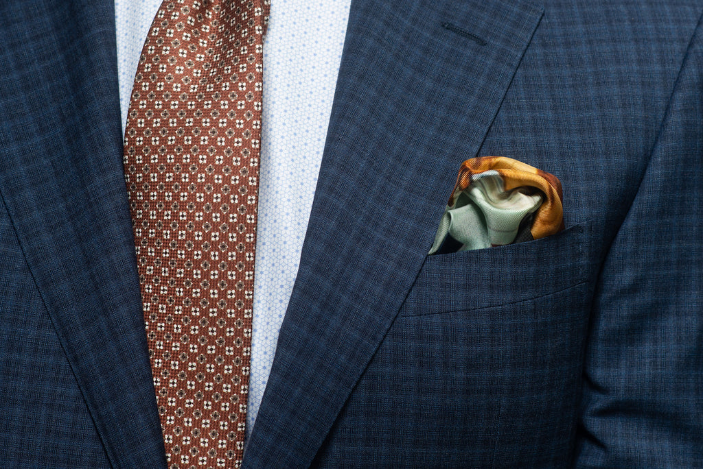 Rust tie with navy check suit and pocket square with rust tones