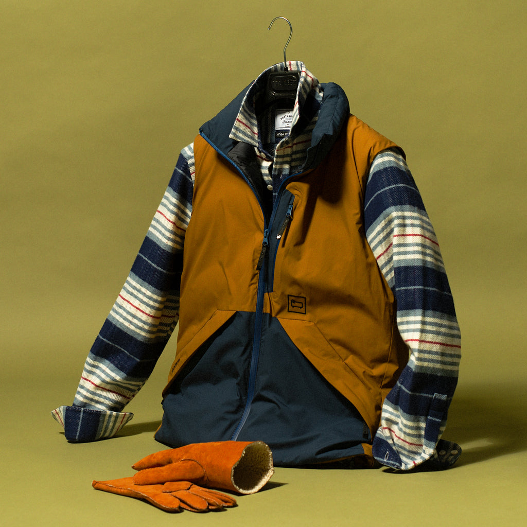 Navy and khaki vest hanging on hanger with striped flannel shirt underneath and gloves on the ground beside it and