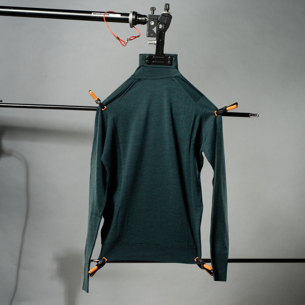 Essential orion green roll neck sweater against grey background