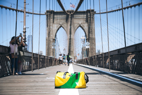 M24 yellow and green tarpaulin bag placed on the ground on the brooklyn bridge