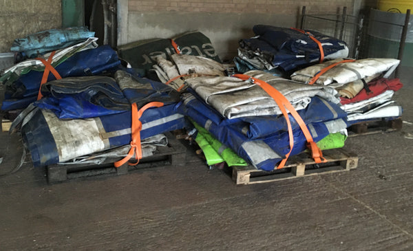 Trailer curtains strapped to pallets with orange ratchet straps. Recycled by M-24
