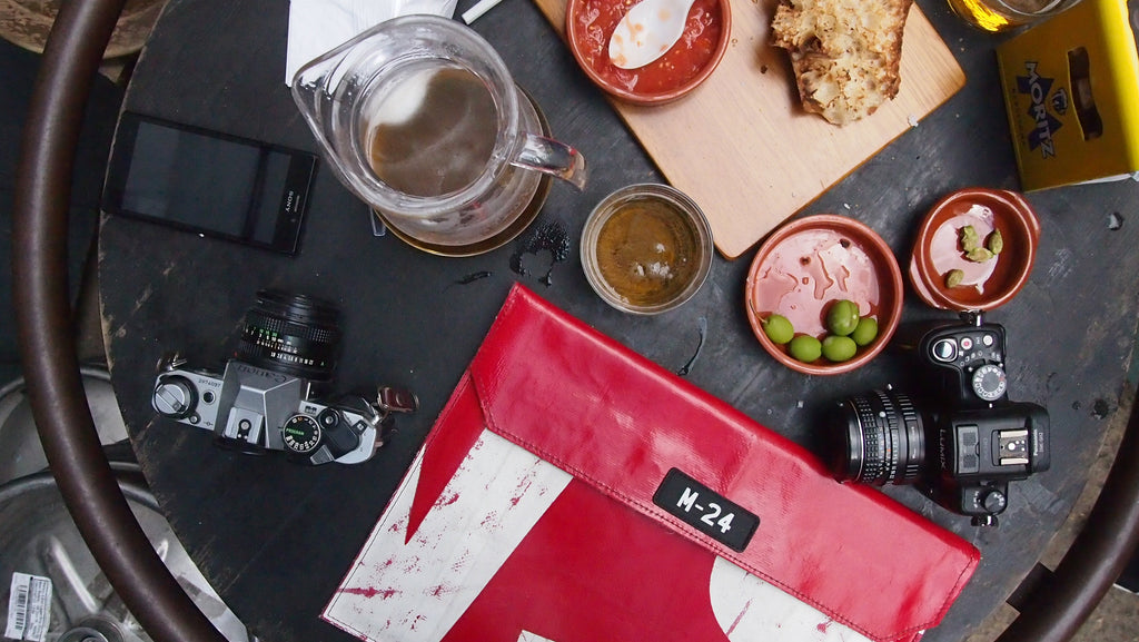 m24 upcycled tarpaulin macbook sleeve on a table with beer and snacks