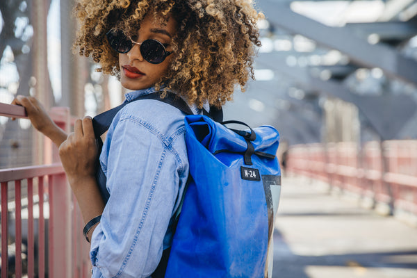 blue upcycled backpack hanging out on a bridge in new york city