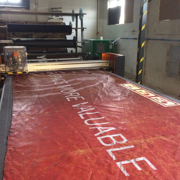 upcycled truck tarpaulin being cut on a laser cutting machine