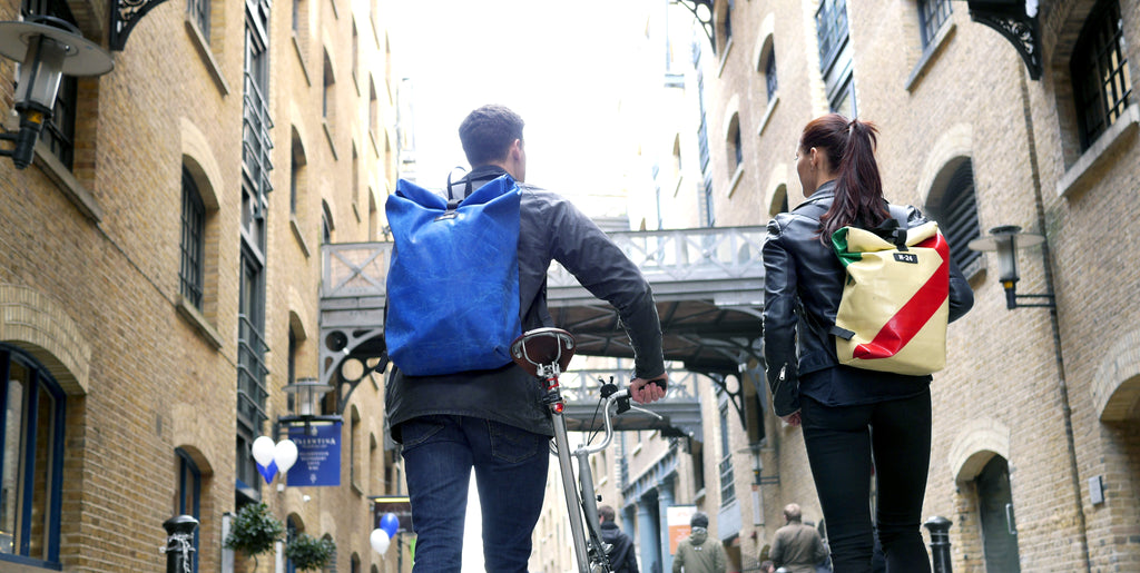 Couple walking through london bridge wearing tough lorry tarpaulins bags