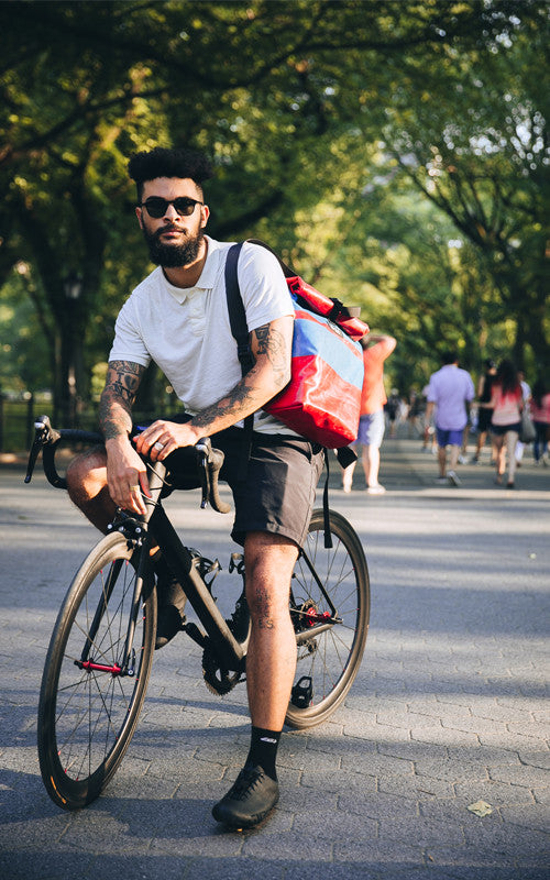 fixie cyclist in new york city, central park. Wearing an m-24 backpack