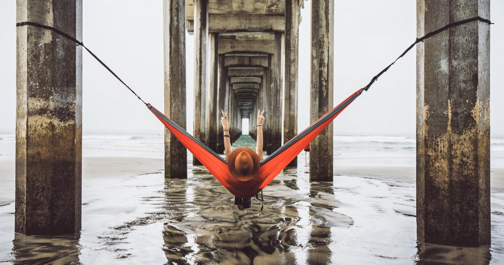 woman wearing a hat hangs from an orange hammock on pillars beneath a pier at the beach