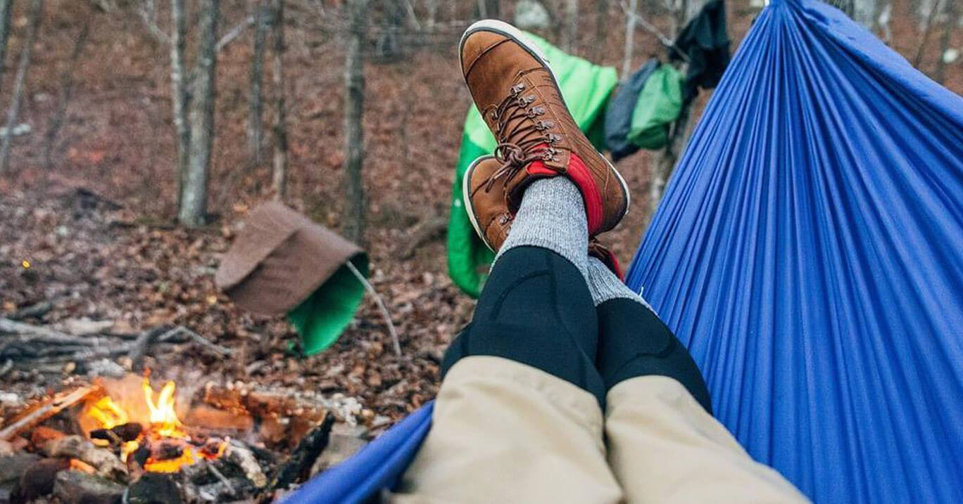 b501183fc41 Person lies on their blue hammock in the woods with their hiking boots on  and a