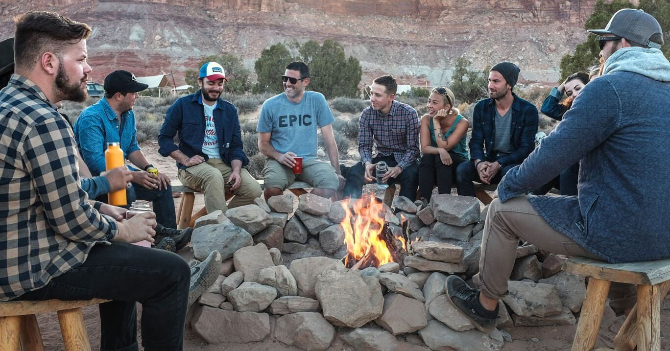 group of millennials camping sitting around a camp fire