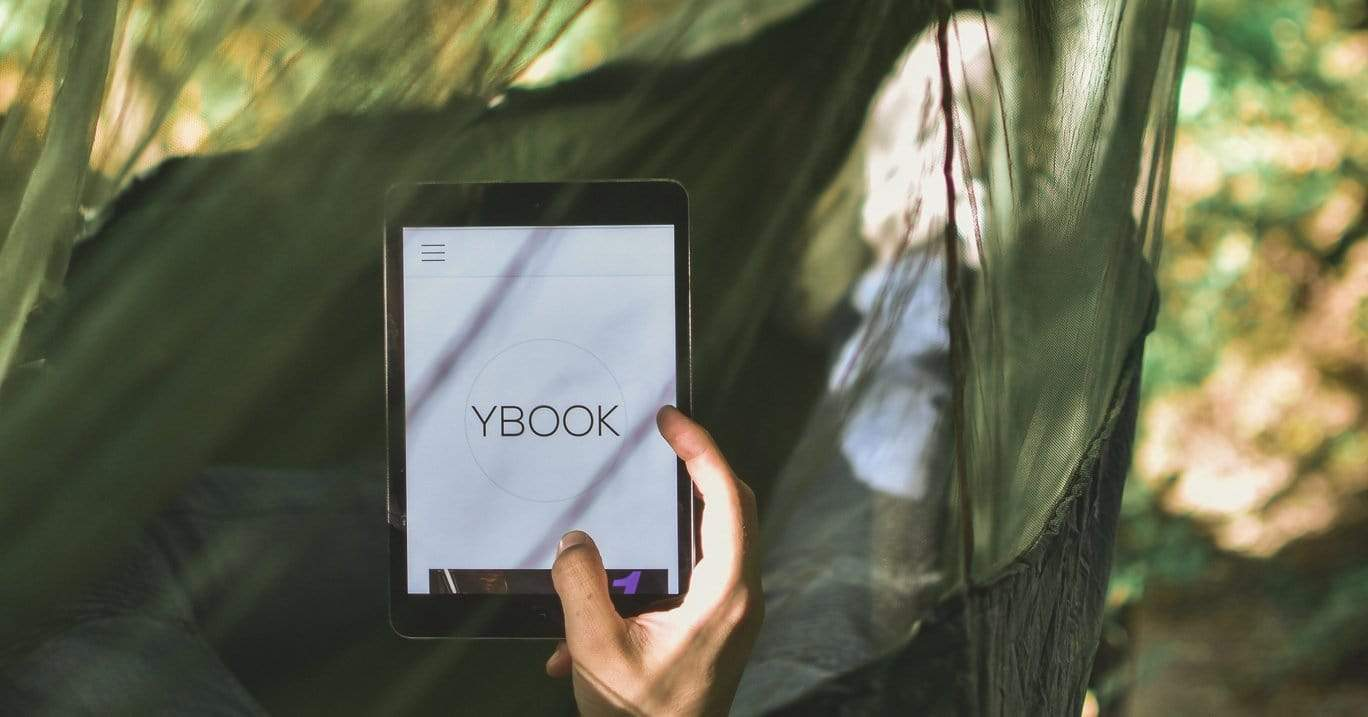 Person lying in an dark green hammock with a netted hammock tarp draped over it holding an tablet reading an e-book.