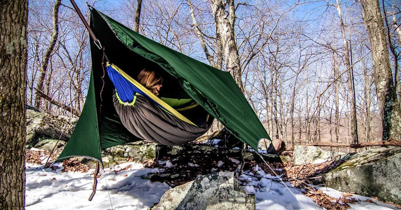 Woman laying in a hammock insulated by a DIY top quilt and underquilt