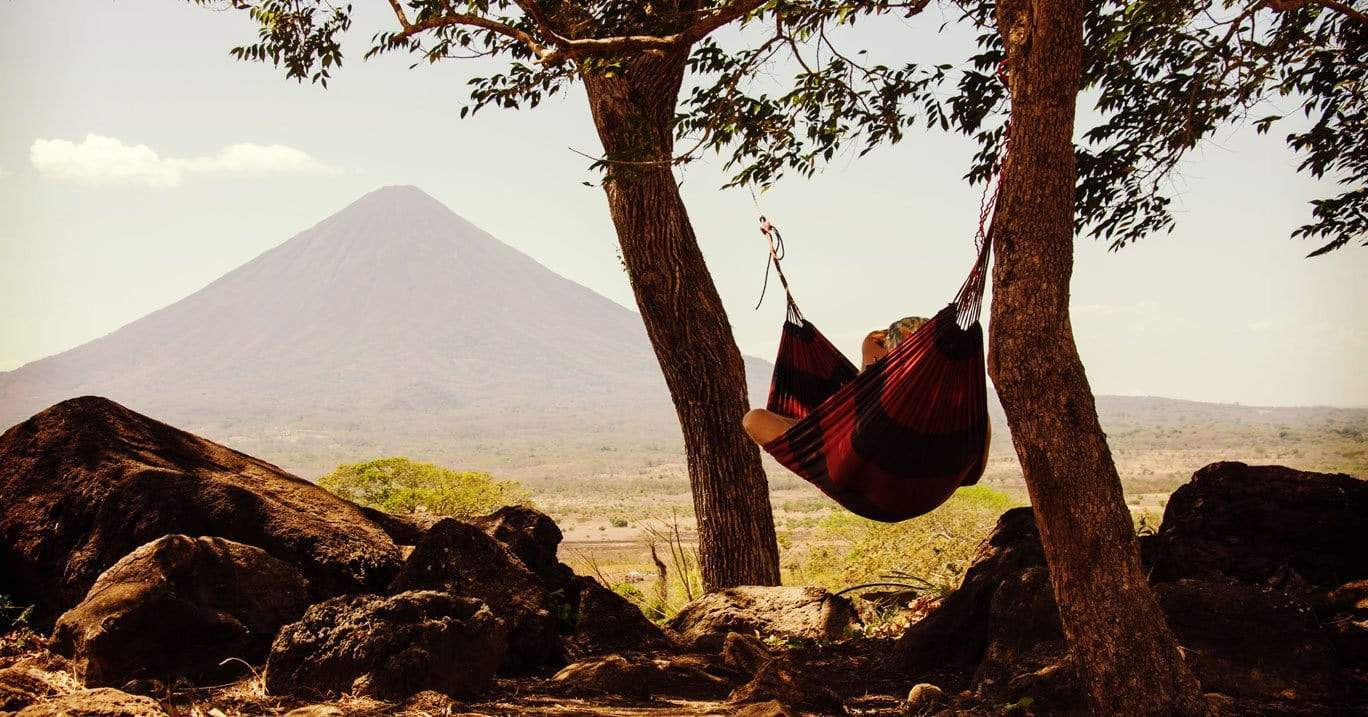person hangs in a Brazilian hammock tucked in between two trees with a mountain in the distance