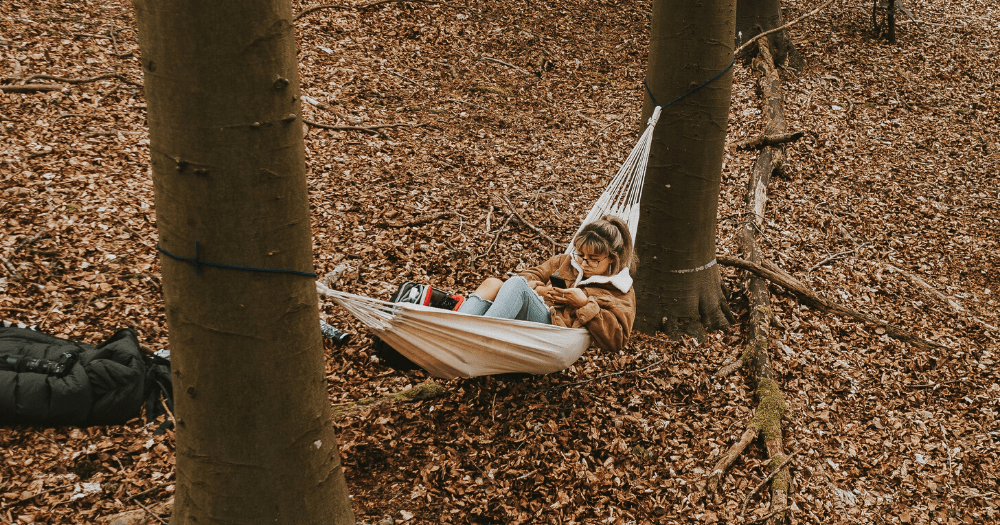 Young woman texts in a Colombian hammock in the forest
