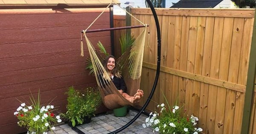 young woman sits in a Mayan hammock chair with universal stand in her backyard next to plants and flowers