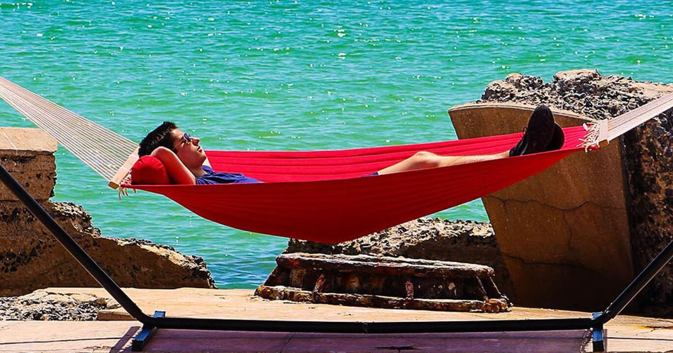 man lounging in a red hammock with three beam stand