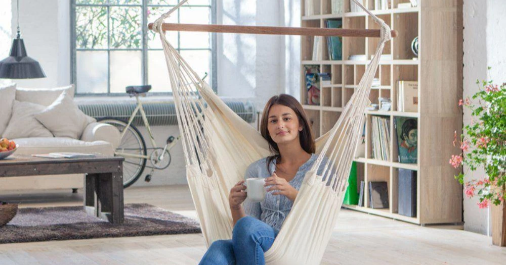 woman enjoying a hot beverage while sitting in a Colombian hammock chair in her living room