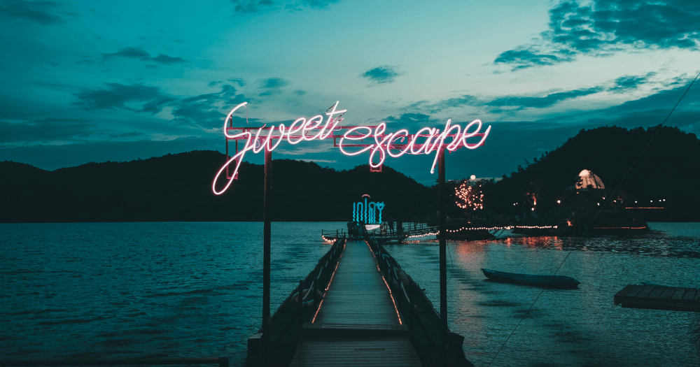 Sweet escape sign in neon pink over the harbor of an island at dusk