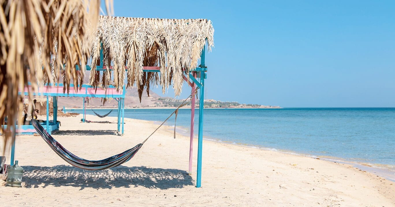 beach cabanas with hammocks next to a crystal clear ocean