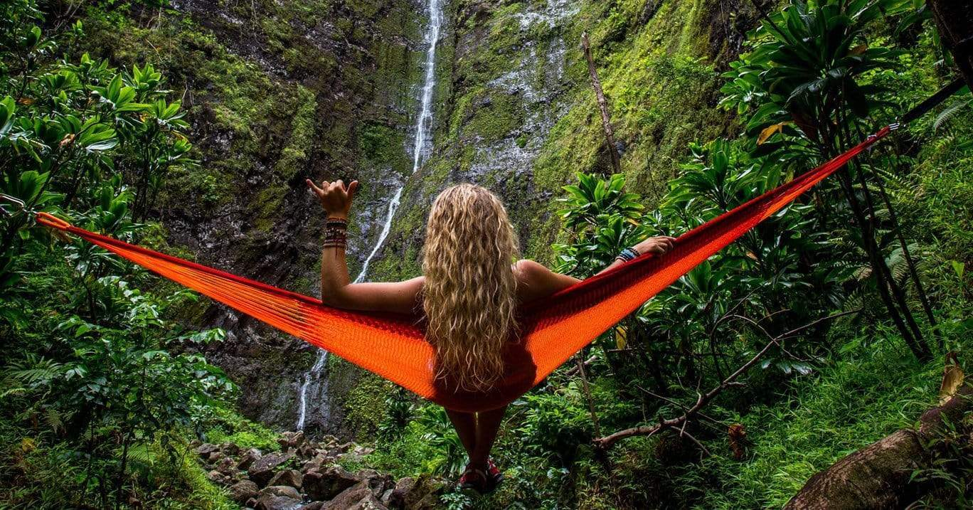 A woman hangs in an orange hammock outdoors in front of a waterfall.