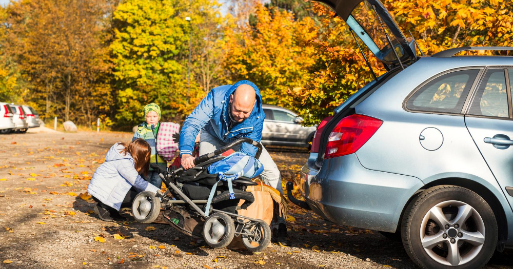 middle-aged man loads stroller into car with the help of his wife